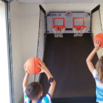 two kids playing a basketball arcade game