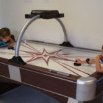 two kids playing air hockey