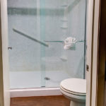 guestroom bathroom with standing shower and toilet